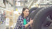 протектор : girl in a plaid shirt buys spike winter tires in a store Стоковые видеозаписи