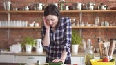 empregada : Woman in a shirt with a bad headache in the kitchen cuts vegetables