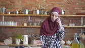 arab woman cooking : Young muslim woman talking on the phone and preparing food in the kitchen