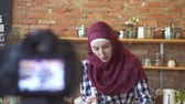 dish photo : Muslim woman in hijab blogger in the kitchen in front of the camera talks about cooking