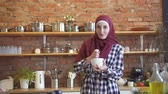 arab woman cooking : Pretty muslim young woman in a scarf prepares in the kitchen