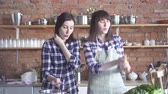 expressando positividade : cute girls dancing and singing in the kitchen while cooking Vídeos