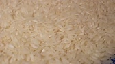 Raw rice grains rotating pattern macro texture background backdrop footage video. Stock Footage