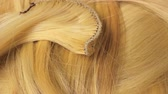 ilustrado : Hair extension cutted hair fibers blonde weft rotating pattern macro texture background backdrop footage video.