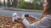 coat : Mother makes footage of baby at autumn park, mobile phone