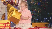 happy new year : Cute little girl unpacking gift box, near decorated Christmas tree Stock Footage