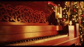 natal árvore : A slow dolly back reveals a vintage piano with a candle burning warmly on top of it, and a beautiful decorated Christmas tree in the background. Very warm tone.