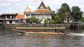 Long tailed boat at engine speed of traffic on the canal in Bangkok