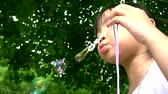 Asian girl playing blowing bubbles in the garden slow motion