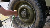 young man cleaning the wheel of the vehicle, slow motion Wideo
