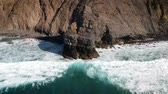 algarve : Aerial done shot of whitewater waves hitting a cliff on the shore of a beach in Algarve, Portugal.
