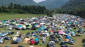 éjszakai : Aerial drone shot of a camping ground at a music festival in a green and lush mountainous area.