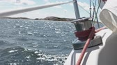 casco : A winch on the railing of the deck of a white sailing boat at sea - slowmotion footage.