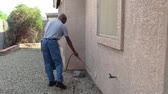afro americana : Male senior citizen using a do-it-yourself pest control  kit to spray the side of his house in the backyard. Stock Footage