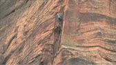 šplhat : Rock Climber repelling down a 200 foot rock face in Zion National Park Utah
