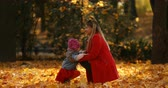 Blonde woman in red coat greeting her daughter in autumnal park.