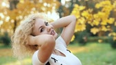 Beautiful blonde woman touching curly hair, walking in autumn park. Stok Video