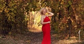 Beautiful and sexy blonde woman in long red dress walking in autumn park.
