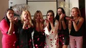 Fashionable women having fun in hotel, blowing red confetti at camera.