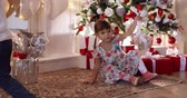 Children with Christmas presents under the Christmas tree. Stock Footage