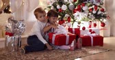 Children with Christmas presents under the Christmas tree. Stok Video