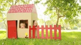 pasture : Video of happy little children sitting in playhouse