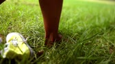 ниже : Sneaker dropping in grass, girl walking slow motion