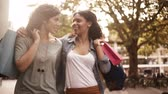 shopping : Mixed race girl friends walking in city urban area with shopping bags and talking Stock Footage