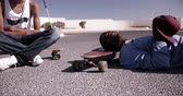 asphalt : Teenage longboarder sitting and lying on their longboards  in Slow Motion