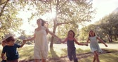 teenager : Young mother running with kids  holding hands through a sunlit park in slow motion