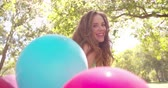 holding : Happy girl holding a bunch of balloons in a park on a summer day in a park in Slow Motion