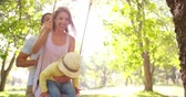 field : Happy family with a little girl toddler swinging in the park together in slow motion
