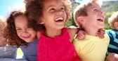 outdoors : Happy mixed racial group of friendly children sitting in the sun laughing together Panning in Slow Motion Stock Footage