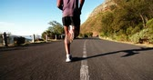 fitness : Jogger running along mountain road in slow motion