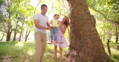 little : Happy parents swinging their cute laughing toddler under a tree in a park in slow motion