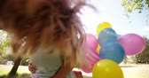 holding : Happy little girl and her mom spinning together in a sunny park with balloons in slow motion Stock Footage