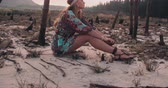 não urbano : Full body shot of a boho girl in a floral dress sitting in a natural landscape in Slow Motion