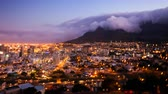 city lights : Timelapse of Cape Town and the Table Mountain during sunset and nightfall, all city lights illuminated and the signature tablecloth clouds coming over the mountain