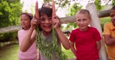 vegetable : Cute little hispanic boy being fun and silly by holding up two carrots like bunny ears and making a funny face, with two of his friends standing on either side in a summer park Stock Footage