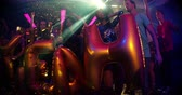 evet : A cheerful group of young adults at party holding inflatable balloons spelling out yeah in a popular trendy nightclub.