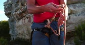 carbine : Detail of climber hands and a carabiner tying a knot with rope before climbing a rock.