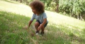 sister : A cute little boy with afro hair is sitting on grass and is running over to his familiy.
