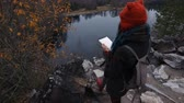 rascunho : artist girl painting sitting on the rocks at the cliff, notepad. Wonderful fall view