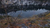 Lovely view of the lake with emerald hill, surrounded by cliffs. Nobody here. Forest reflection in water. Stock Footage