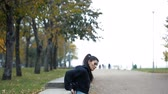 Portrait of woman in sportswear, doing fitness push-ups exercise at fall park, outdoor.