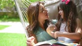 contar : Beautiful mother with daughter reading book on backyard, sitting in hammock and talking with pleasure, enjoying happy family life.Full HD Video 1920x1080 Stock Footage