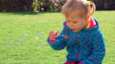 Cute little girl playing outdoors, adorable sweet baby with pleasure blowing soap bubbles on backyard. Full HD Video 1920x1080