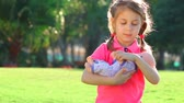 Cute little girl having fun with doll outdoors, playing in daughters-mothers game, happy summer time activity, slow motion. Full HD Video 1920x1080