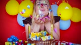 fajerwerki : Beautiful happy girl enjoying her birthday party, laughing and having fun, blowing many shiny tinsel, slow motion. Full HD Video 1920x1080