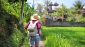 Traveler woman with backpack walking in the fresh green tropical lands, active lifestyle, happy summer vacation in Asia. Full HD Video 1920x1080